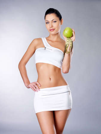 cocnept: Healthy girl with apple and measuring tape. Healthy lifestyle cocnept.