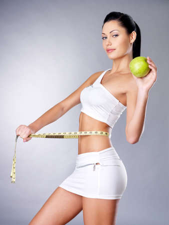 cocnept: Slimming woman measures figure with a measuring tape and holding the apple. Healthy lifestyle cocnept.