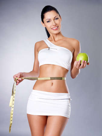 Slimming woman with a measuring tape and apple. Healthy lifestyle for female. photo