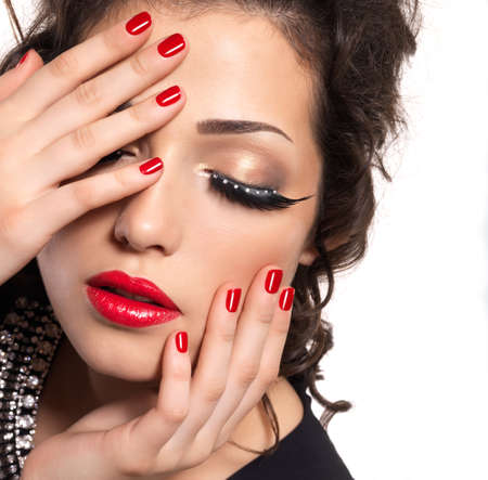 nail colour: Beautiful fashion model with red nails, lips and creative eye makeup  - isolated on white background Stock Photo