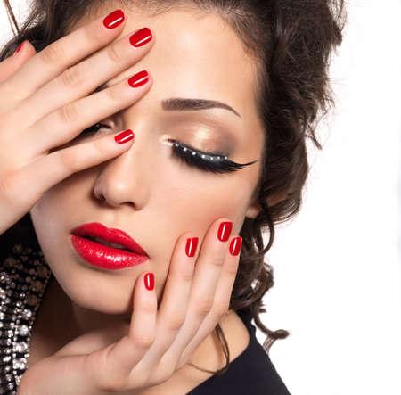 pestaÑas postizas: Modelo de manera hermosa con las uñas, los labios rojos y el maquillaje del ojo creativo - aislados en fondo blanco