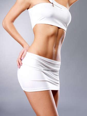 허리의 잘룩 한 선: 흰색 스포츠 옷에서 아름 다운 건강한 여성의 몸 스톡 사진