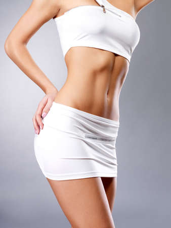 is slender: Beautiful healthy female body in white sport clothes