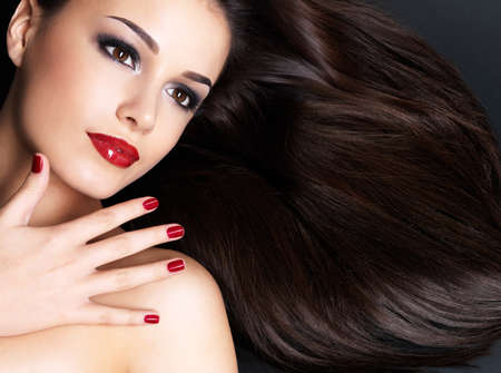 beautiful face: Beautiful woman with long brown straight hairs and red nails lying on the dark background