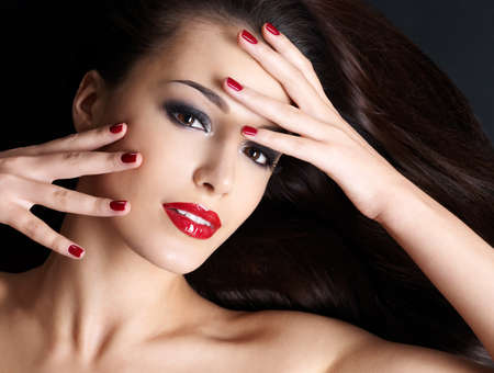 dark brown hair: Beautiful woman with long brown straight hairs and red nails lying on the dark background