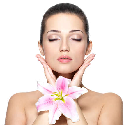 Beauty face of young woman with flower. Beauty treatment concept. Portrait of young woman with closed eyes photo