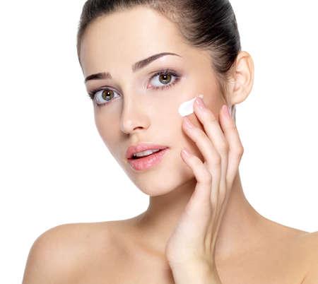Belleza rostro de mujer joven con crema cosmética en una mejilla. Cuidado de la piel concepto. Retrato del primer aislado en blanco.