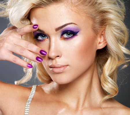 eyeshadows: Beautiful blond woman with beauty purple manicure and makeup of eyes. Fashion model with curly hairstyle. Stock Photo