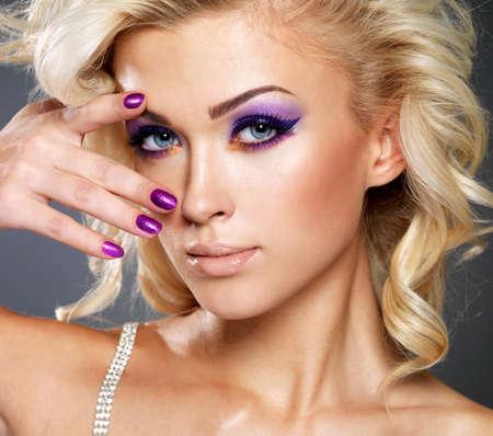 maquillaje de ojos: Mujer rubia hermosa con la manicura y maquillaje púrpura belleza de los ojos. Modelo de manera con el peinado rizado.
