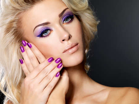 Beautiful blond woman with beauty purple manicure and makeup of eyes. Fashion model with curly hairstyle. photo