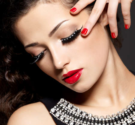 Fashion woman with modern creative makeup using false eyelashes red manicure photo