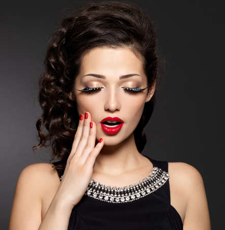 Young pretty woman with red manicure,  lips and creative eye makeup.  Fashion model with bright expressions Stock Photo - 16858853
