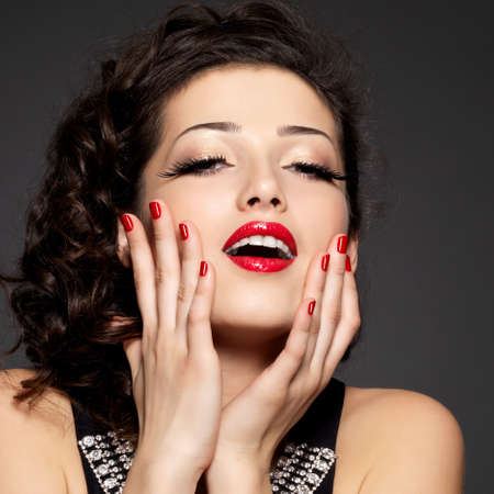 red nails: Young pretty woman with red manicure and  lips.  Fashion model with bright positive emotions