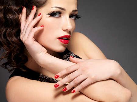 maquillage yeux: Mode femme de beaut� avec des ongles rouges, les l�vres et maquillage pour les yeux d'or - sur fond noir