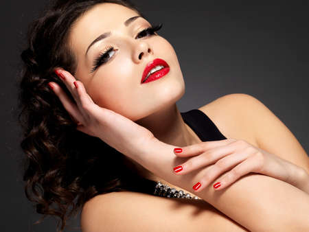 Beauty fashion woman with red nails, lips and golden eye makeup  - on black background Stock Photo - 16858861