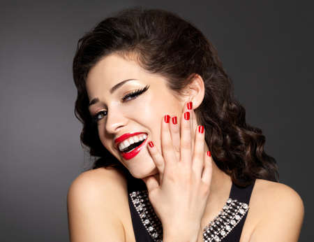 Young pretty woman with red manicure and  lips.  Fashion model with bright positive emotions Stock Photo - 16764883