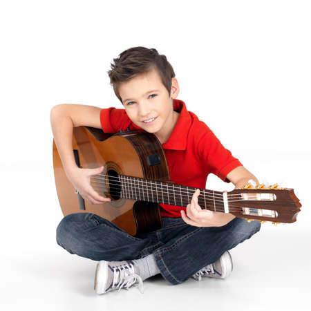 Knappe gelukkige jongen speelt op akoestische gitaar - geïsoleerd op witte achtergrond