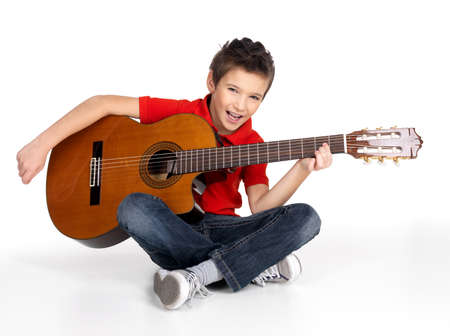 Pretty boy is playing the acoustic guitar - isolated on white background photo