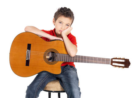 disinclination: Sad white boy with a  acoustic guitar in his hands  The child does not want to be engaged in music  - isolated on white background