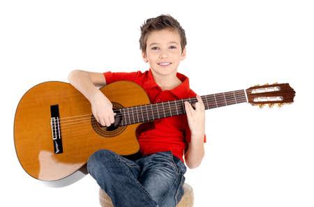 guitarra acustica: Ni�o feliz hermoso est� jugando en la guitarra ac�stica - aislados en fondo blanco Foto de archivo