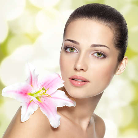 beautiful girl face: Beauty face of young woman with flower. Beauty treatment concept. Blinking Background. Bokeh