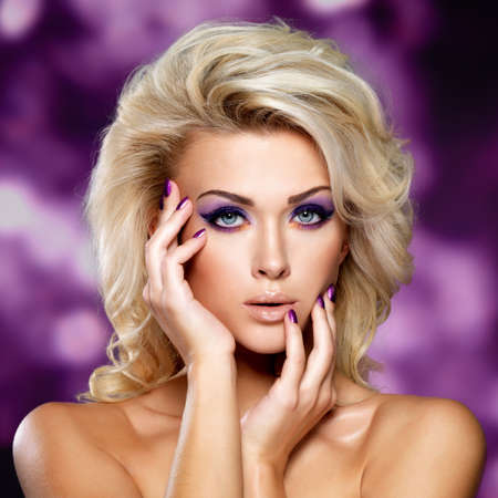 nail studio: Beautiful blond woman with  purple makeup of eyes. Fashion model with curly hairstyle. Blinking Background. Bokeh Stock Photo