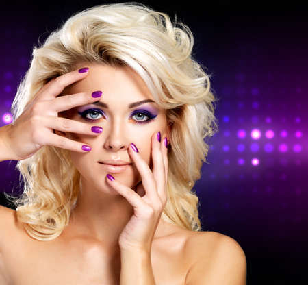 Beautiful blond woman with beauty purple manicure and makeup of eyes. Fashion model with curly hairstyle. Blinking Background. Bokeh photo