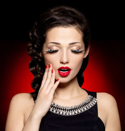 Young pretty woman with red manicure,  lips and creative eye makeup.  Fashion model with bright expressions photo