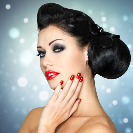 nails woman: Beautiful fashion woman with red lips, nails and creative hairstyle.  Blinking Background. Bokeh