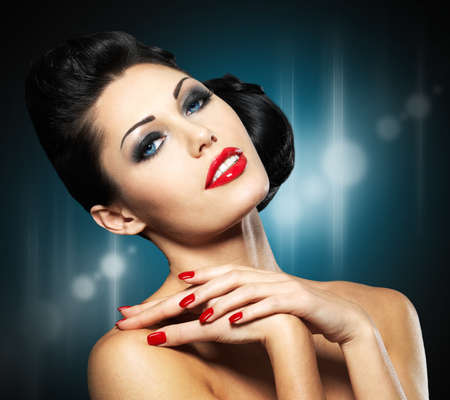 creative: Beautiful fashion woman with red nails, creative hairstyle and makeup. Blinking Background. Bokeh