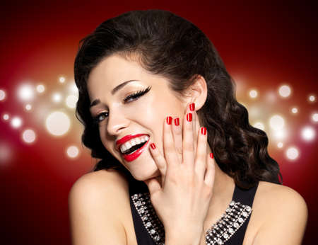 Beautiful woman with red manicure and  lips.  Fashion model with bright positive emotions. Blinking Background. Bokeh photo