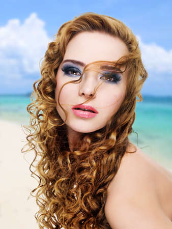 Beautiful glamour  woman with  long curly hairs and bright  make-up. Portrait on the nature background. photo