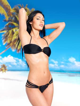 thin: Woman with beautiful body in black bikini sunbathe on the beach