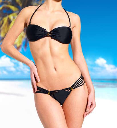 muslos: hermoso cuerpo delgado de la mujer en bikini en la playa Foto de archivo