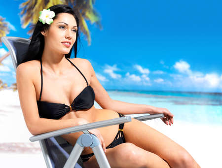 Young beautiful woman enjoying at beach sitting on chair photo