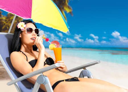 sunbathe: Happy brunette woman on vacation drinking orange juice on the beach