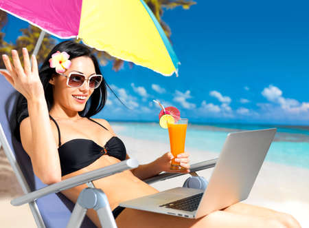 Happy woman on the beach with a laptop computer. Vacation and communication concept. photo