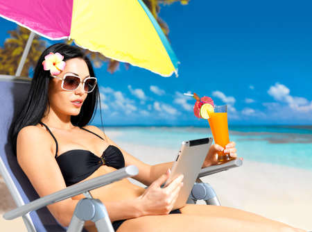 Beautiful woman on the beach with ipad. Vacation and communication concept. photo