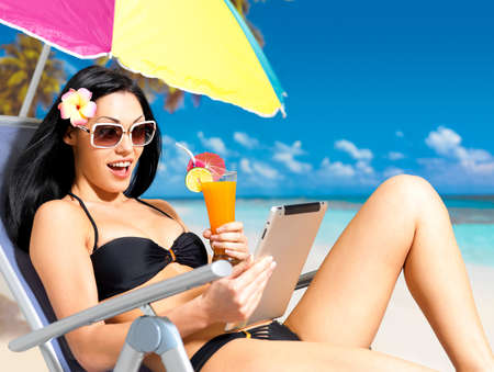Happy woman on the beach with ipad. Vacation and communication concept. photo