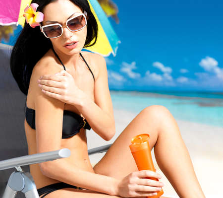 tanned body: Beautiful young woman in black bikini applying sun block cream on the tanned body.  Girl  holding orange sun tan lotion bottle.