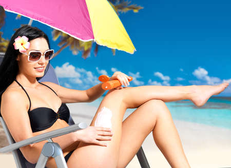 Beautiful happy woman in black bikini applying sun block cream on the tanned body.  Girl  holding orange sun tan lotion bottle. photo