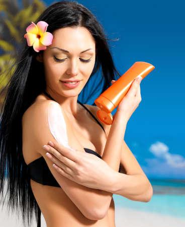 Beautiful young woman in black bikini applying sun block cream on the tanned body.  Girl  holding orange sun tan lotion bottle.