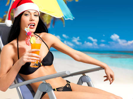 Happy woman celebrating the new year at the beach. A beautiful girl in the santa hat with a refreshing drink in hand. photo