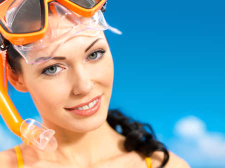 Portrait of the happy beautiful woman enjoying at beach. Pretty girl with a protective swim mask on the head. photo