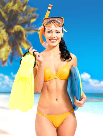 Happy beautiful woman enjoying at beach. Pretty girl with a protective swim mask on the head. Stock Photo