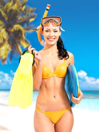 flippers: Hermosa mujer feliz disfrutando en la playa. Muchacha bonita con una máscara protectora de natación en la cabeza.