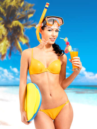 Happy beautiful woman enjoying at beach. Pretty girl with a protective swim mask on the head. photo