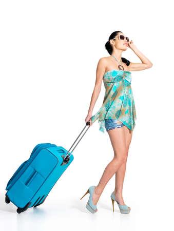 De cuerpo entero de la mujer ocasional de pie con la maleta de viaje - aislados en fondo blanco
