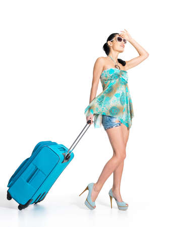 Full length of casual woman standing with travel suitcase - isolated on white background