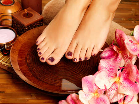 spa therapy: Closeup photo of a female feet at spa salon on pedicure procedure. Legs care concept